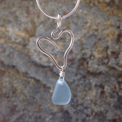 Pale blue Guernsey sea glass pendant suspended below a sterling silver heart.