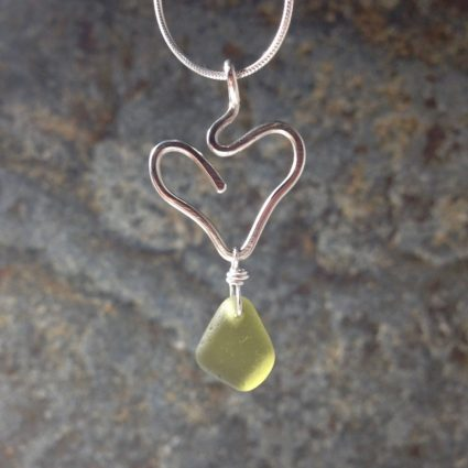 Lime green Guernsey sea glass pendant suspended below a sterling silver heart.