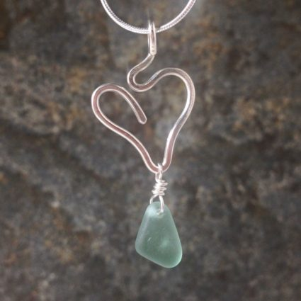 Turquoise Guernsey sea glass pendant suspended below a sterling silver heart.