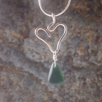 Olive green Guernsey sea glass pendant suspended below a sterling silver heart.