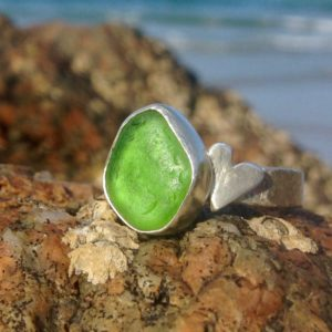 Emerald green Guernsey sea glass ring with sterling silver band and heart detail.