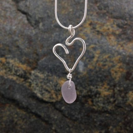 Pale rose Guernsey sea glass pendant suspended below a sterling silver heart.