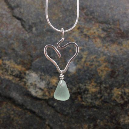 Seafoam Guernsey sea glass pendant suspended below a sterling silver heart.